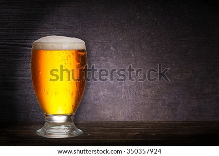 Glass of beer on dark wooden background with copyspace