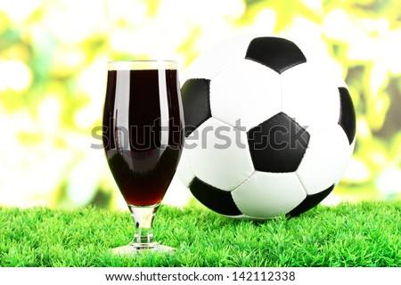 Glass of beer on lawn with ball - stock photo