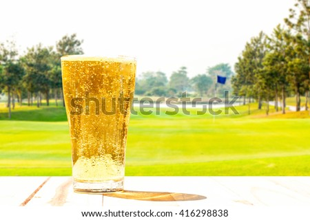 Glass of beer on the background blur of golf. - stock photo