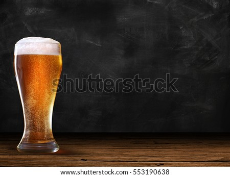 Glass of beer on the left of rustic table and dark chalk background