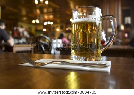 glass of beer on the table in pub close up - stock photo