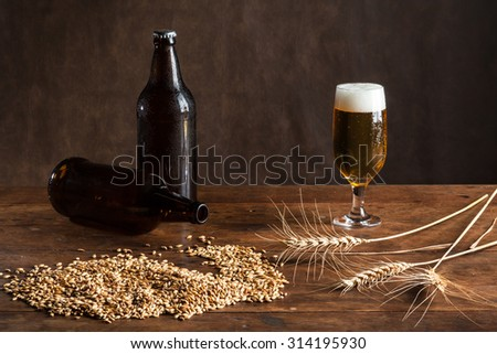 Glass of beer on the table, with wheat malt, barley and bottles - stock photo