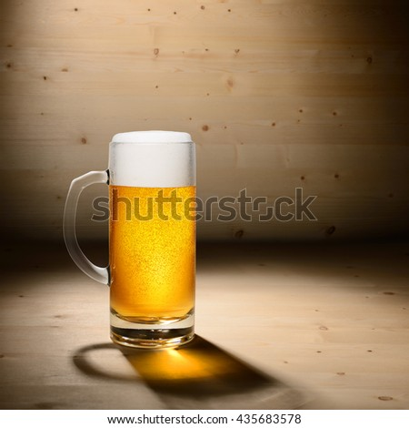 Glass of beer on wood background with copyspace
