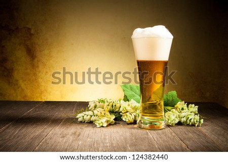 Glass of beer on wooden table - stock photo