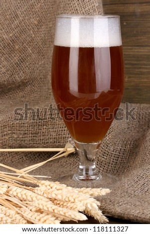 Glass of beer on wooden table on sacking background
