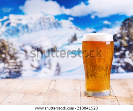 glass of beer on wooden table over winter landscape - stock photo