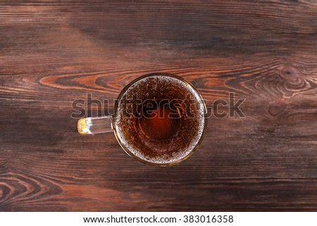 Glass of beer on wooden table, top view - stock photo