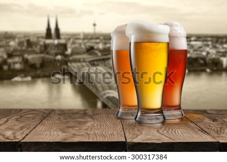 Glass of beer on wooden table with view of Koln on background, Germany - stock photo