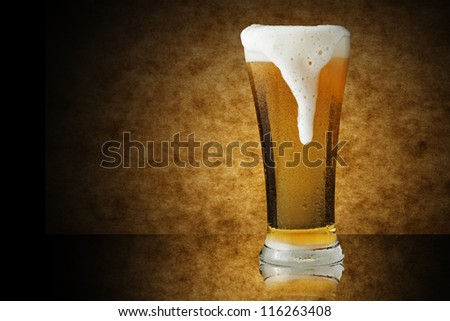 Glass of beer on yellow wooden background