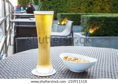 Glass of beer serve with snack on a table in a bar - stock photo