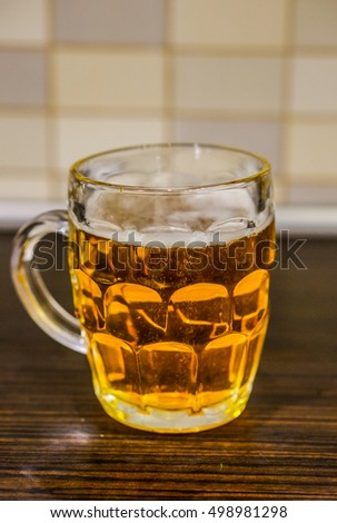Glass of beer standing on wooden table