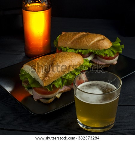 Glass of beer, tasty sandwiches with baguette, ham, tomato, onion, cucumber and lettuce and beer bottle on wooden table. Fast food. Focus on sandwich. - stock photo