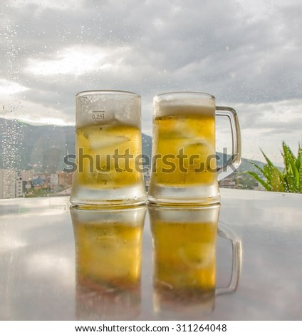 glass of beer with bar scene in the background - stock photo