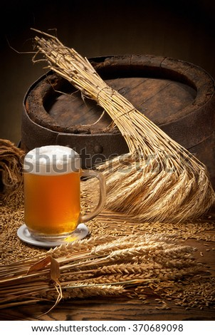 glass of beer with barley and wheat on the wooden barrel