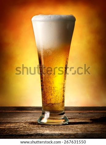 Glass of beer with bubbles on a wooden table - stock photo