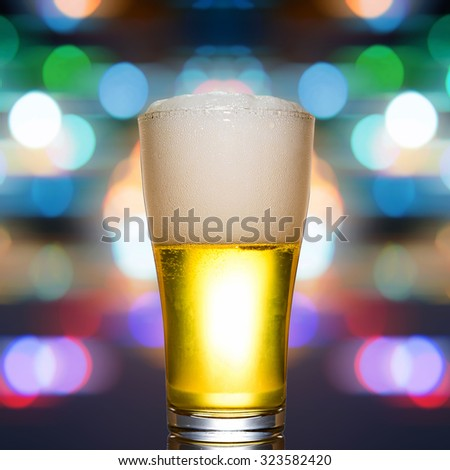 glass of beer with colorful bokeh background - stock photo