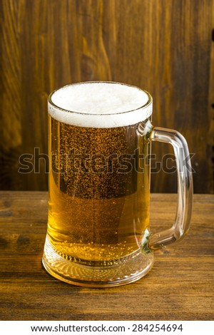 glass of beer with foam deposited on the wooden table