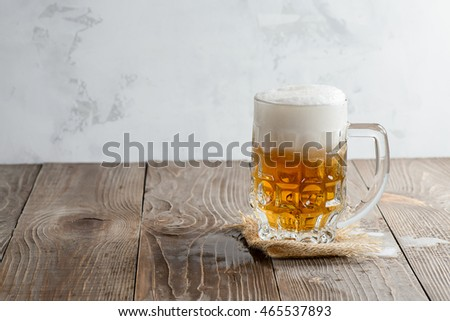 Glass of beer with foam on a wooden background
