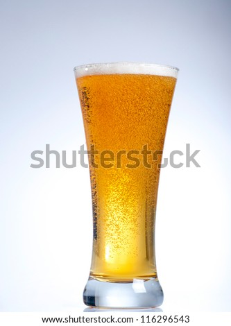 Glass of beer with froth close up on white