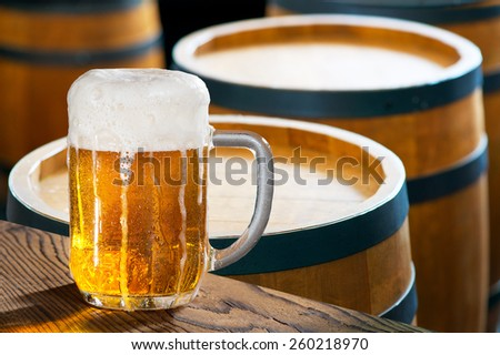 glass of beer with old wooden barrels - stock photo