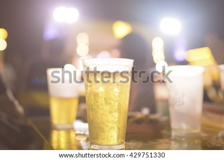Glass of beer with party scene in the background - stock photo