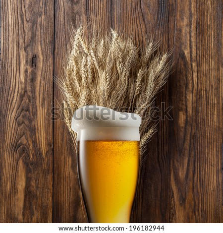 Glass of beer with wheat on wooden background - stock photo