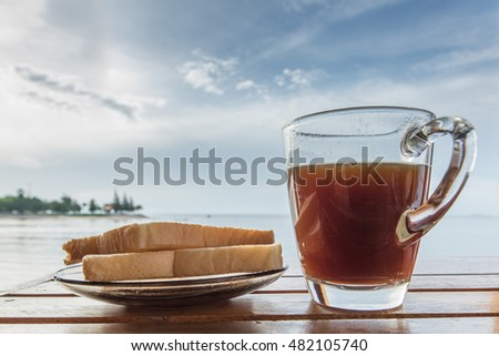 glass of black coffee and pieces of bread