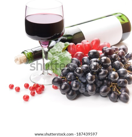 Glass of black wine and grapes on white background