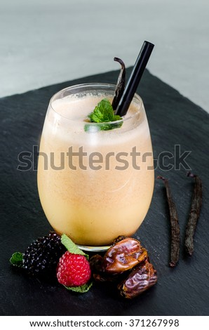 glass of blended fresh fruit vegetable juice vanilla bean dates coconut milk on black stone plate straw - stock photo