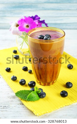 Glass of blueberry smoothie on wooden table, closeup