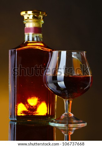 Glass of brandy and bottle on brown background - stock photo
