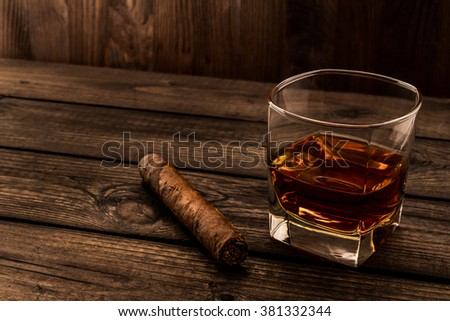 Glass of brandy and cuban cigar on an old wooden table. Angle view