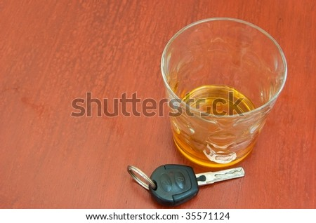 Glass of brandy and keys on a bar - stock photo