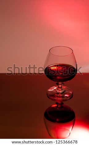 glass of brandy on red background - stock photo