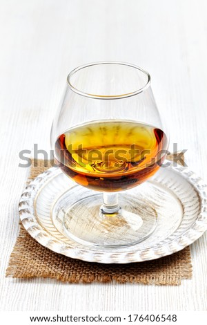 glass of brandy on white wooden table - stock photo
