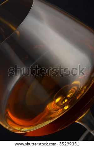 Glass of brandy over black background