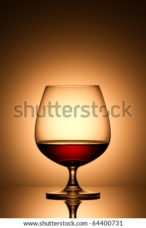 Glass of brandy over gold background