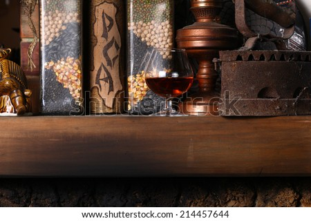 Glass of brandy standing on a fireplace shelf with various vintage objects