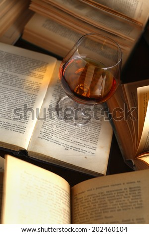 Glass of brandy standing on open books