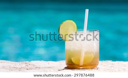 Glass of Caipirinha cocktail on the pool nosing at the tropical resort. Horizontal, wide screen, cocktail on right side - stock photo