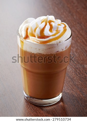 glass of caramel latte coffee on wooden table - stock photo
