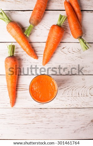 Glass of carrot juice and carrots on the white table - stock photo