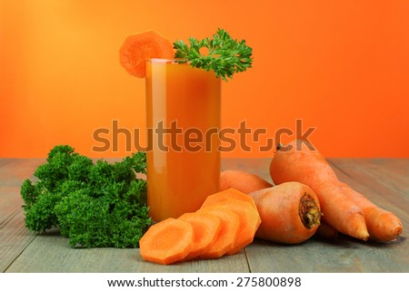Glass of carrot juice and fresh carrots on wooden background - stock photo