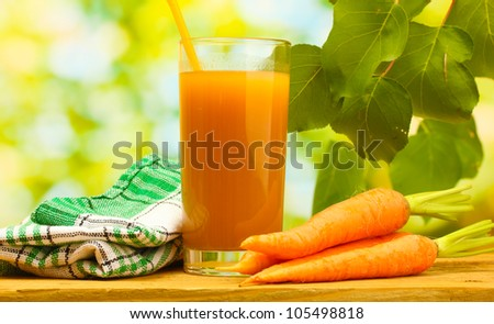 glass of carrot juice and fresh carrots on wooden table on green background - stock photo