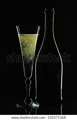 Glass of champagne and  bottle. Close up. Black background - stock photo