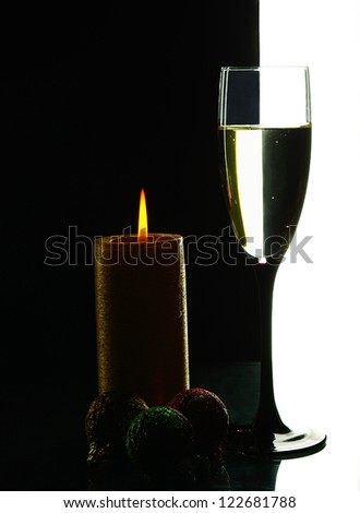 Glass of champagne and  candle. Black and white background