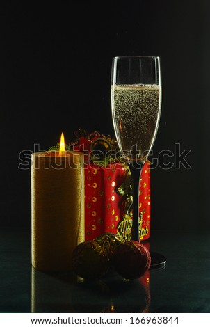 Glass of champagne and candle with festive background