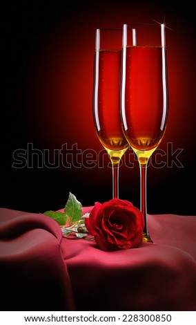 glass of champagne and red rose on black background