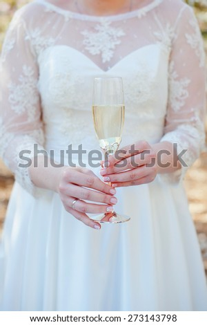 Glass of champagne in hands of the bride. Wedding rings. - stock photo