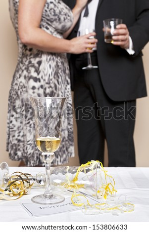 Glass of champagne on a table with an invitation and guests drinking in the background, focus is on the foreground. Good image for a Wedding, Party or New Year Eve theme.